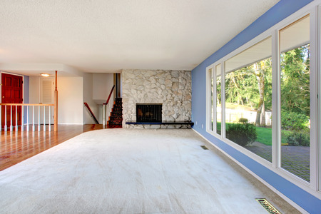 Refreshing empty living room with blue walls, big window and carpet floor. View of the entrance hallway photo