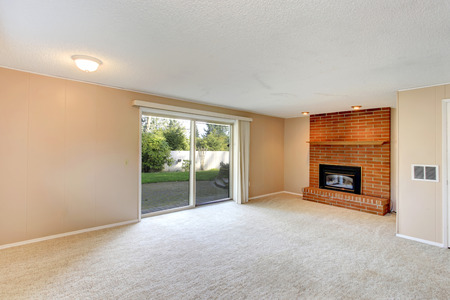 Empty living room with a brick background fireplace, carpet floor and walkout deck photo