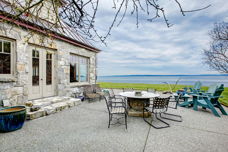 porches: VIew of the big stone house with concrete floor patio area. Patio table set and deck chairs.