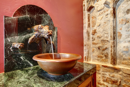 vessel sink: Beautiful antique washbasin cabinet with a stoned dragon head, vessel sink and green marble counter top. Castle style stone wall