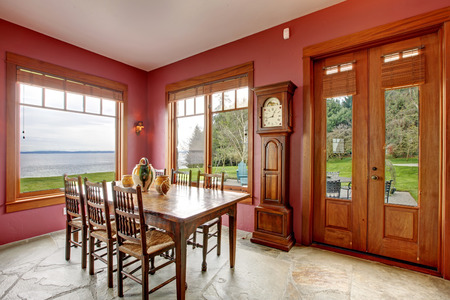grandfather clock: Spacious dining room with walkout deck. Furnished with rustil old table set, grandfather antique clock.
