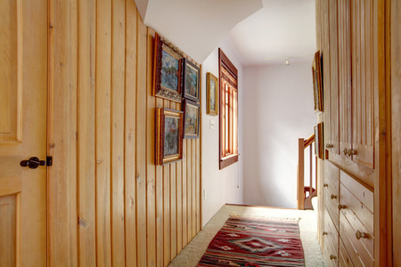 Narrow wood plank paneled hallway with a carpet floor,  old style rug, wooden built-ins Banque d'images