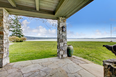 curb appeal: Beautiful open stone porch with columns. Porch overlooking picturesque landscape.