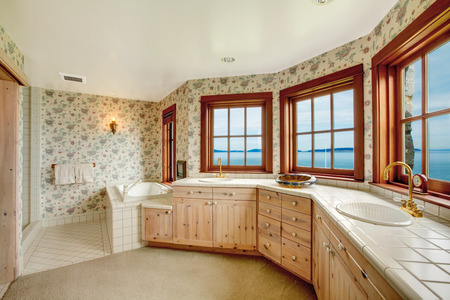 Floral walls bathroom with french windows, tile and carpet floor. View of wood plank paneled storage combination Stock Photo - 26537111