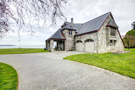 two car garage: Impressive stone house with column porch, two car garage and driveway