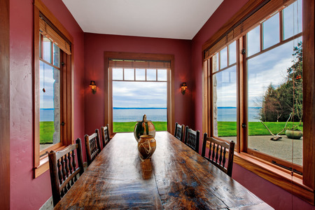 Antique style dining room with rustic table set, burgundy walls and windows Stock Photo - 26537131