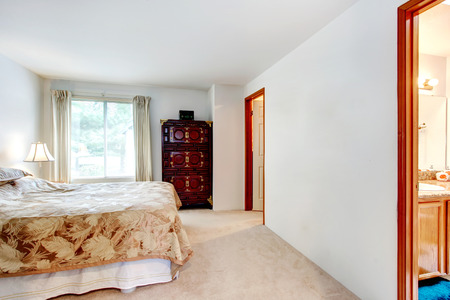 Beige carpet floor master bedroom with a queen size bed and an antique dresser photo