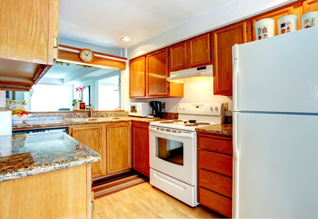 Open wall small kitchen room with a hardwood floor, wooden cabinets and white appliances photo