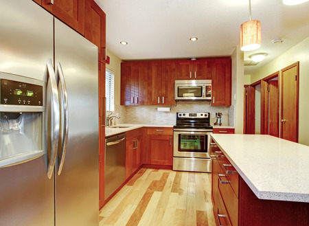 Small kitchen with hardwood floor, cherry cabinets and steel appliances