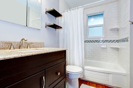 Bathroom with window, dark brown washbasin cabinet, whtie tub and toilet