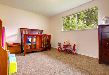 designer baby: Simple baby room with cherry wood crip and toys Stock Photo