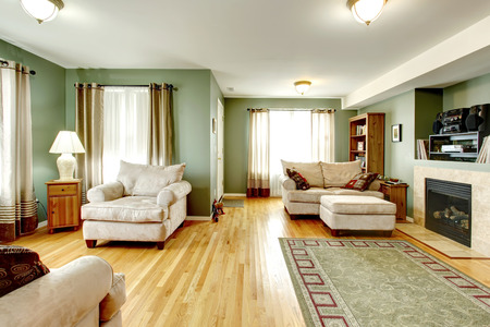 Cozy living room with a hardwood floor, fireplace. Furnished with armchair, love seat and foot-rest. photo