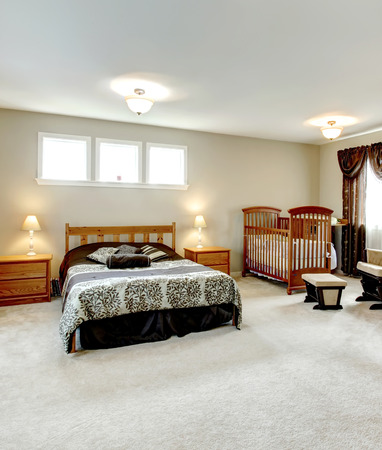 Big master bedroom with a walk-in closet. Nursery corner with a crib. photo
