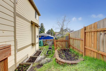 fenced: Green fenced backyard with flower bed and small garden bed Stock Photo