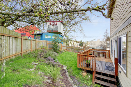 fenced: Fenced backyard with flower bed and wooden walkout deck