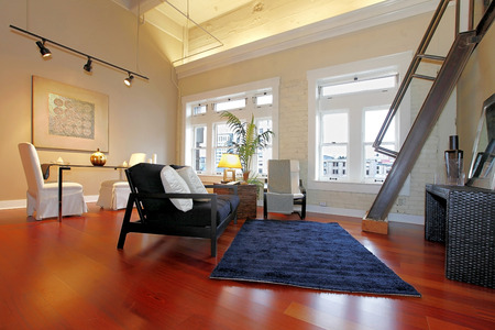 Modern living room with brick painted wall, high ceiling, hardwood floor and iron steep stairs. Furnished with classic elegant furniture photo