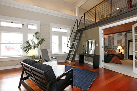 Modern living room with brick painted wall, hardwood floor and iron steep stairs. View of bedroom photo