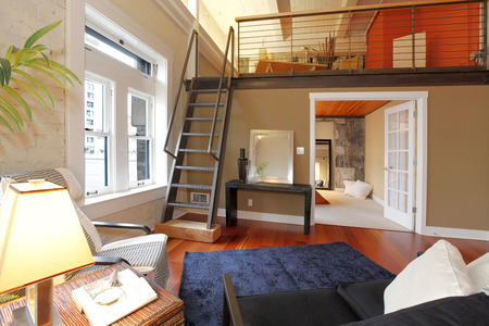 View of modern reconstructed living room with mezzanine area above bedroom. View of iron steep stairs Stock Photo