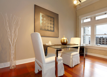 Elegant glass table with white luxury chairs in modern reconstructed living room. Decorated with glass vase and white dry branches and wall picture photo