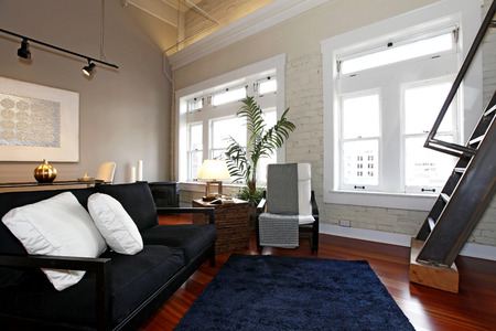 Reconstructed modern living room with brick painted wall, hardwood floor and high ceiling. View of black classic couch, windows and steep iron stairs photo