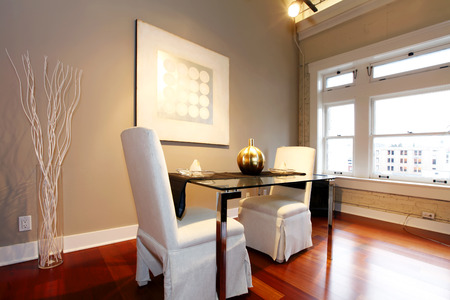reconstructed: Elegant glass table with white luxury chairs in modern reconstructed living room. Decorated with glass vase and white dry branches and wall picture
