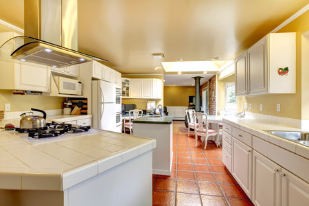 kitchen tile: Ivory wall kitchen room wtih white storage combination and brown tile floor. View of the dining area