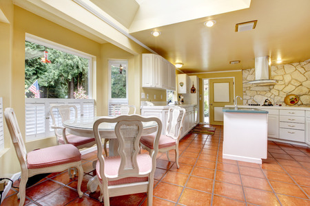 Bright ivory kitchen room with white cabinets and tile floor. View of the antique wooden table set photo