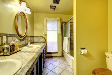 Spacious bathroom with concrete floor and stone wall trim. photo