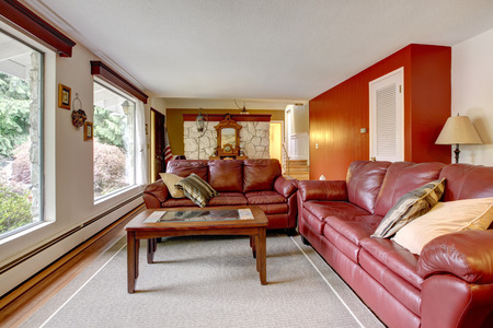 trim wall: Luxury living room with stone wall trim . Furnished with burgundy leather couches and coffee table.