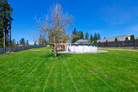 fenced: Fenced backyard with green lawn and deck. Stock Photo