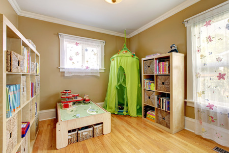 Gentle kids room with floral curtains, storage units and wicker baskets  photo