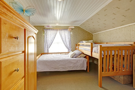 Low vaulted ceiling room with carpet floor and wallpaper wall  Furnished with two beds and dresser photo