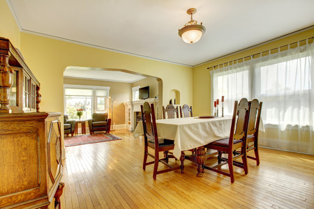 Beautiful elegant dining room with antique carved wood table set and cabinet photo