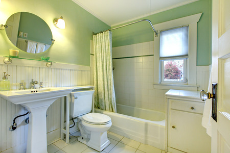 Mint bathroom with light green curtains, tile floor and wood plank wall trim  View of sink, toilet and bath tub