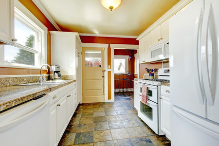 Orange walls kitchen room with concrete floor  Furnished with white storage combination  View of small dining area photo