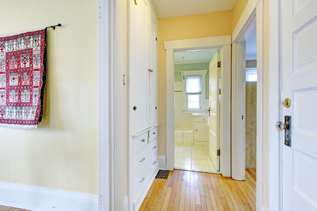 Bright narrow corridor with hardwood floor and white built-ins  photo