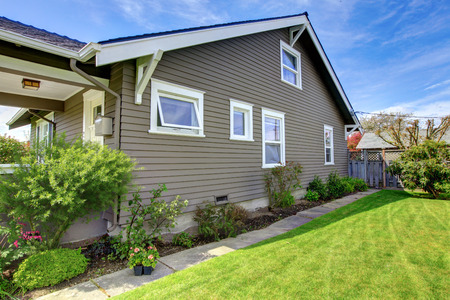 View of the clapboard siding house socle with white windows and green lawn  Stok Fotoğraf