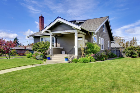 흰색 열 poch과 녹색 잔디의 기와 지붕과 벽돌 굴뚝 전망 닿은 딩 집