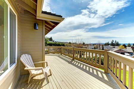 wood deck: Wooden walkout deck with a chair overlooking road and neighborhood Stock Photo