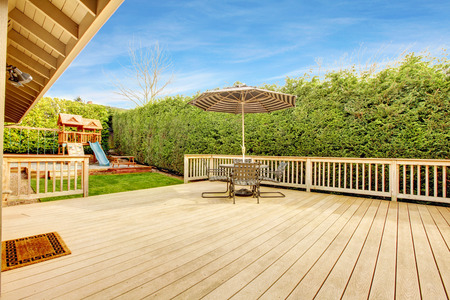Spacious wooden deck with umbrella and patio table set. View of play yard with chute photo