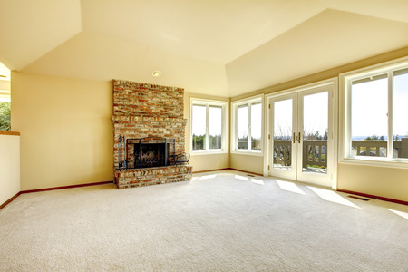 Bright empty living room with high vaulted ceiling and carpet floor. View of brick background fireplace and walkout deck photo