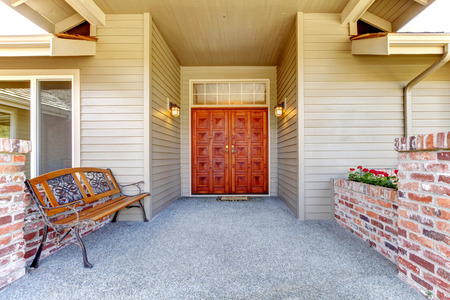 trim wall: Clapboard siding house entrance porch. Brick trim wall blend perfectly with antique iron bench Stock Photo