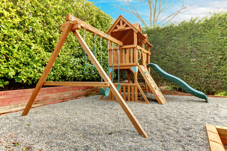 Backyard playground with swings, climbing wood panel, chute.