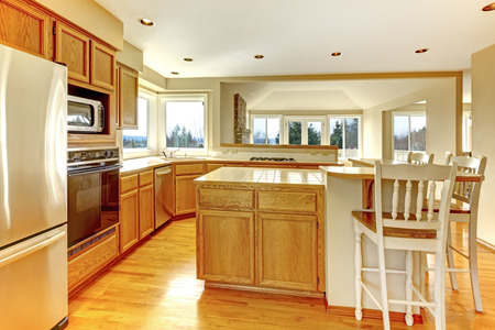 counter top: Bright kitchen room with windows. View of cabinets and counter stools