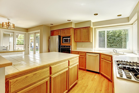 counter top: Bright kitchen room with windows and walkout deck  View of kitchen island and cabinets