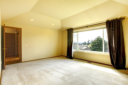 brigth: Brigth empy room with high vaulted ceiling and beige carpet floor  View of window with curtains Stock Photo