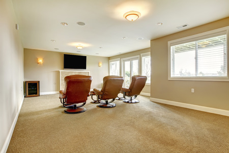 Cozy home theater with fireplace and three leather amrchairs with foot-rests