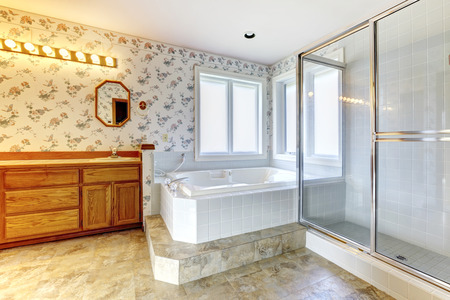 Spacious bathroom with floral wallpaper, concrete floor and windows  View of white  tub, glass door shower and wooden cabinets photo