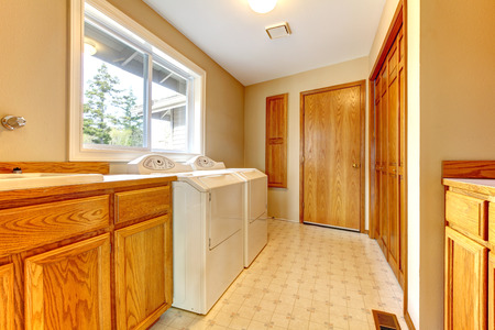 Narrow laundry room with a window  Furnished with washbasin cabinet, dryer and washer Stock Photo - 26606653