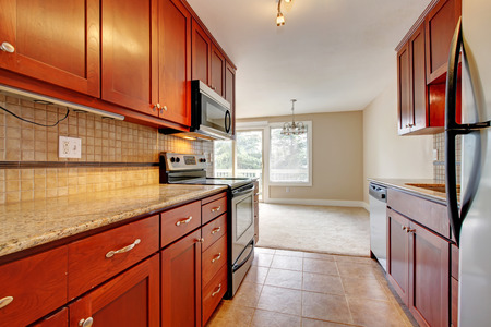 back kitchen: Modern kitchen interior  Cherry wooden cabinets with marble counter tops blends with steel appliances